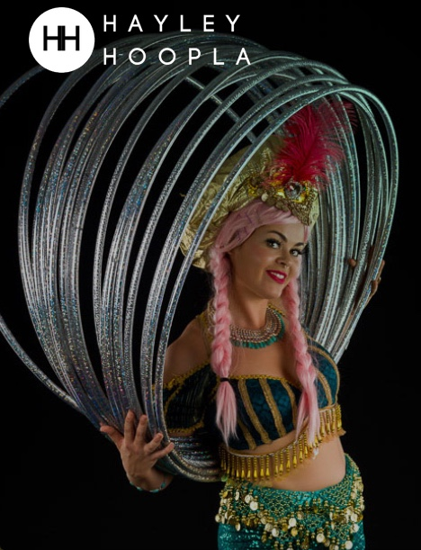 image features a woman in a sparkling costume with silver hula hoops