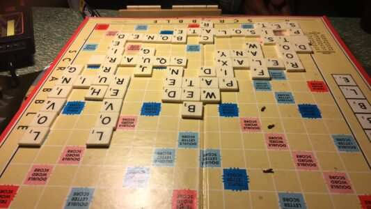 image features an English-language Scrabble board with a game in progress
